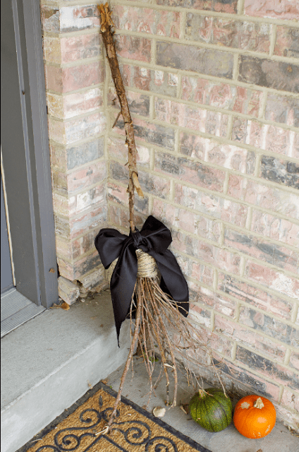 A witches broom leaning against a wall, by a front door